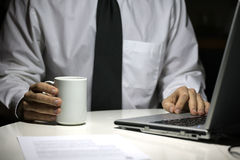 Business man with coffee cup working on laptop Royalty Free Stock Images