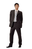 Business man of coldness. Full length portrait of Asian office worker in formal suit standing and showing unfriendly expression, isolated on white background Royalty Free Stock Photography