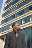 Business Man Contemplating Future. A professional man looks into the future in front of an office building Stock Photo