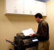 Business man at copy machine. Business man checking work at copy machine against background color of brown tones Royalty Free Stock Images