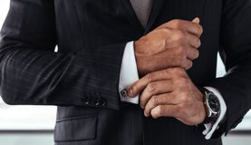Business man correcting a sleeve. Closeup of businessman in formal suit correcting a sleeve. Male hands fixing white shirt cuffs sleeves Stock Photography