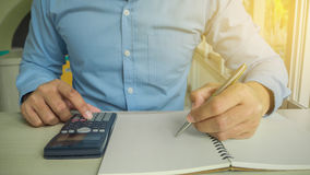 Business man counting on calculator sitting Stock Photos