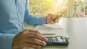 Business man counting on calculator sitting at the table. Royalty Free Stock Images