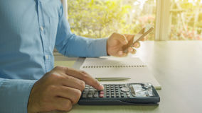 Business man counting on calculator sitting at the table Royalty Free Stock Image