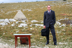 Business man in countryside. With his suitcase stock image