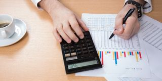 business man counts on a close-up calculator, cafe, laptop, business, finance, banking royalty free stock photos