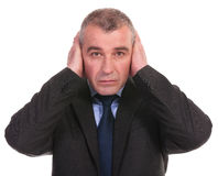 Business man covers his ears Stock Photos