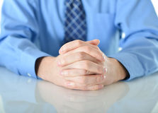 Business man with crossed hands resting on table. Successful business man with crossed hands resting on table Royalty Free Stock Photo
