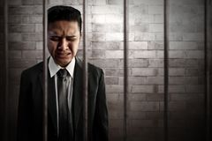 Businessman crying in prison stock images