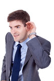 Business man cupping hand behind ear Royalty Free Stock Image