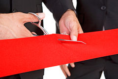 Business: Man Cuts Through Red Ribbon with Scissors Stock Photos