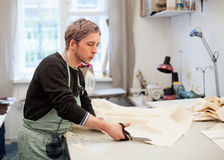Business. Man cutting fabric in his workshop. Workshop. Young man tailor snipping the cloth Royalty Free Stock Photo