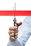 A business man cutting a scarlet satin ribbon Royalty Free Stock Photography