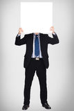 Business man in dark suit holding a blank sign Stock Photo
