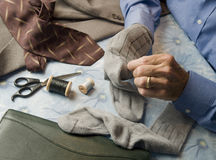 Business man darning socks Stock Photos