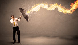 Business man defending himself from a fire arrow with an umbrell Royalty Free Stock Image