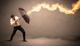 Business man defending himself from a fire arrow with an umbrell. A on grungy background Stock Images