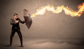 Business man defending himself from a fire arrow with an umbrell Royalty Free Stock Photo