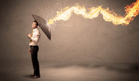 Business man defending himself from a fire arrow with an umbrell Royalty Free Stock Photos