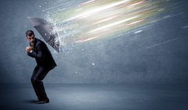 Business man defending light beams with umbrella concept Stock Photo