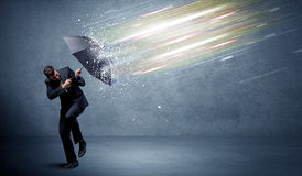 Business man defending light beams with umbrella concept. On background Royalty Free Stock Image