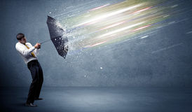 Business man defending light beams with umbrella concept Stock Images