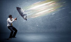 Business man defending light beams with umbrella concept Stock Photography