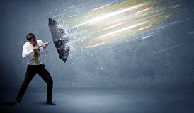 Business man defending light beams with umbrella concept Royalty Free Stock Image