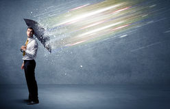 Business man defending light beams with umbrella concept Royalty Free Stock Photography