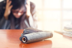 Business man depressed from failure of business and gun on the table, selective focus on front gun. Blank text stock photography