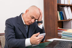 Business man at desk, contemplating your i-pad/tablet. Royalty Free Stock Images