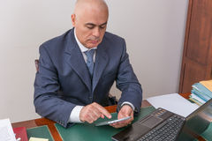 Business man at desk, contemplating your i-pad/tablet. Royalty Free Stock Photos