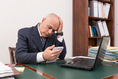 Business man at desk, contemplating your i-pad/tablet. Royalty Free Stock Photography