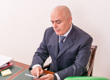 Business man at desk, contemplating your i-pad/tablet. Stock Images