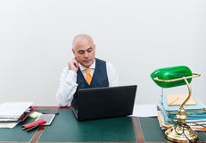 A business man at desk, deep in thought. Stock Photo