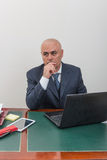 A business man at desk, deep in thought. Royalty Free Stock Image