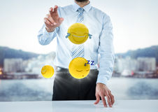 Business man at desk with emojis and flares against blurry skyline. Digital composite of Business man at desk with emojis and flares against blurry skyline Royalty Free Stock Images