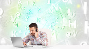 Business man at desk with green word cloud Stock Photo