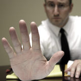 Business Man at Desk Holding Hand Up Royalty Free Stock Images