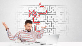 Business man at desk with labyrinth and arrow. Business man at desk with labyrinth in the background stock image