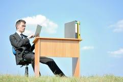 Business man at desk outside Stock Image