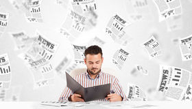 Business man at desk with stock market newspapers Stock Photography