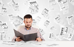 Business man at desk with stock market newspapers Stock Photos