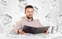 Business man at desk with stock market newspapers Stock Image