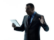 Business man digital tablet. One caucasian business man standing using digital tablet  silhouette  on white background Stock Images