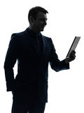Business man  digital tablet smiling  silhouette Stock Images