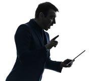 Business man  digital tablet surisped shocked silhouette. One  business man holding digital tablet surisped shocked in silhouette on white background Royalty Free Stock Photos