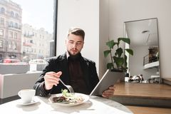 Business man dining in a restaurant and using a tablet royalty free stock image