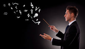 Business man directing lots of symbols. Side view of a young business man directing with a conductor's baton a bunch of symbols stock image