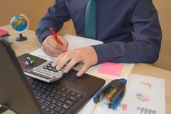 Business man doing finances on calculate analysis working with financial results Financial accounting sales forecast graph. Businessman working in his laptop Royalty Free Stock Photo